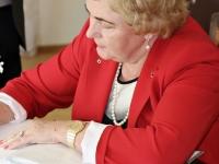 Prezidento našlė pasirašo muziejaus lankytojų knygoje.