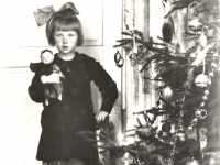 Pirktiniais žaisliukais papuošta eglė Kaišiadorių apylinkės teismo antstolio Jurgio Žitkaus namuose. Prie eglės Aleksandra Žitkutė. Kaišiadorys. 1934 m.